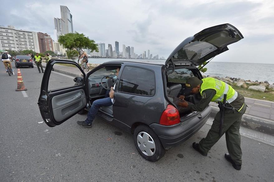 Un policía colombiano revisa un vehículo. Más de 2,500 integrantes de las fuerzas de seguridad resguardarán el evento. (Foto Prensa Libre: AFP).