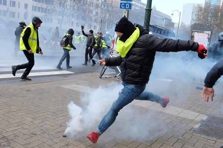 """Un manifestante del colectivo """"chalecos amarillos"""" trata de devolver un cartucho de gas lacrimógeno durante una protesta contra la subida de los impuestos a los carburantes. (Foto Prensa Libre: EFE)"""