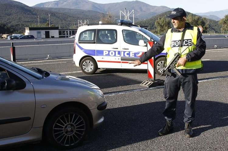 A police officer performs a control stop at the French-Spanish border near Perthus on November 14, 2015. European capitals reinforced security checks as governments held emergency cabinet meetings on November 14 a day after multiple attacks in Paris in which at least 128 people were killed. AFP PHOTO / RAYMOND ROIG