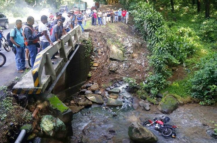 Vecinos observan el cuerpo de Juan José Mérida Hernández, quien cayó junto a su motocicleta en el río Ojo de Agua, Santa Cruz Muluá, Retalhuleu. (Foto: Rolando Miranda)