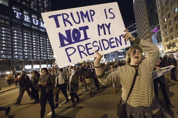 """""""Trump no es mi presidente"""" reza el cartel de una mujer que protesta afuera de la Torre Trump en Chicago. (Foto Prensa Libre: AFP)"""
