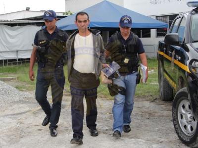 Agentes de policía trasladan a Rafael Santano Asencio y Asencio tras arribar al aeropuerto La Aurora. (Foto Prensa Libre: PNC)