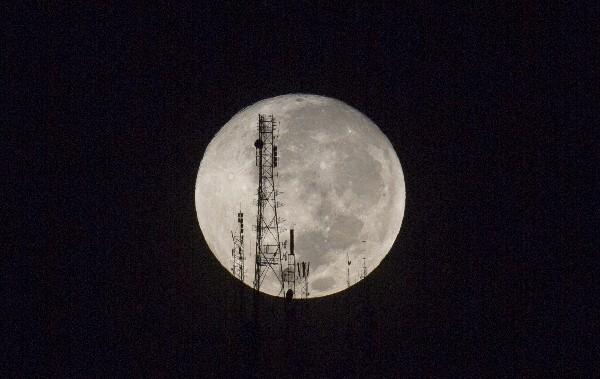 Una luna llena se observa entre las siluetas de antenas de televisión y radio  en Puerto Príncipe, Haití.