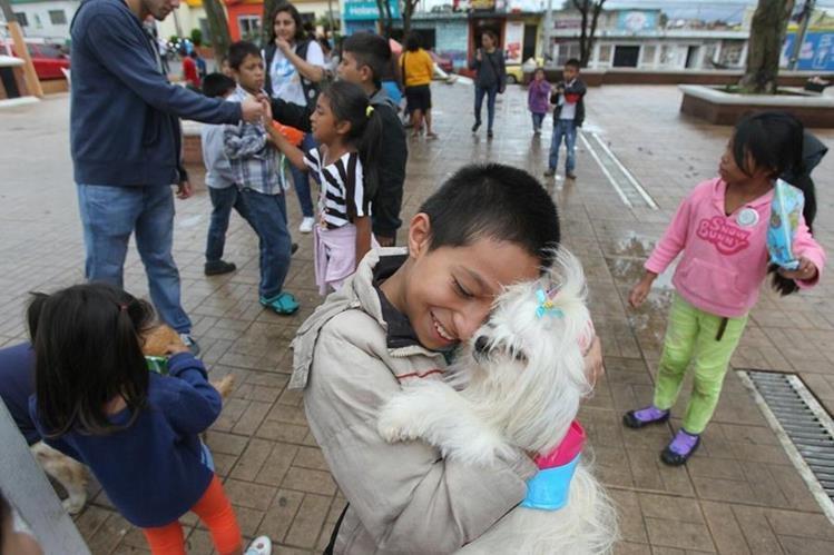 Niños juegan con perros como parte del tratamiento psicológico para superar la tragedia en El Cambray 2. (Foto Prensa Libre: Esbin García)
