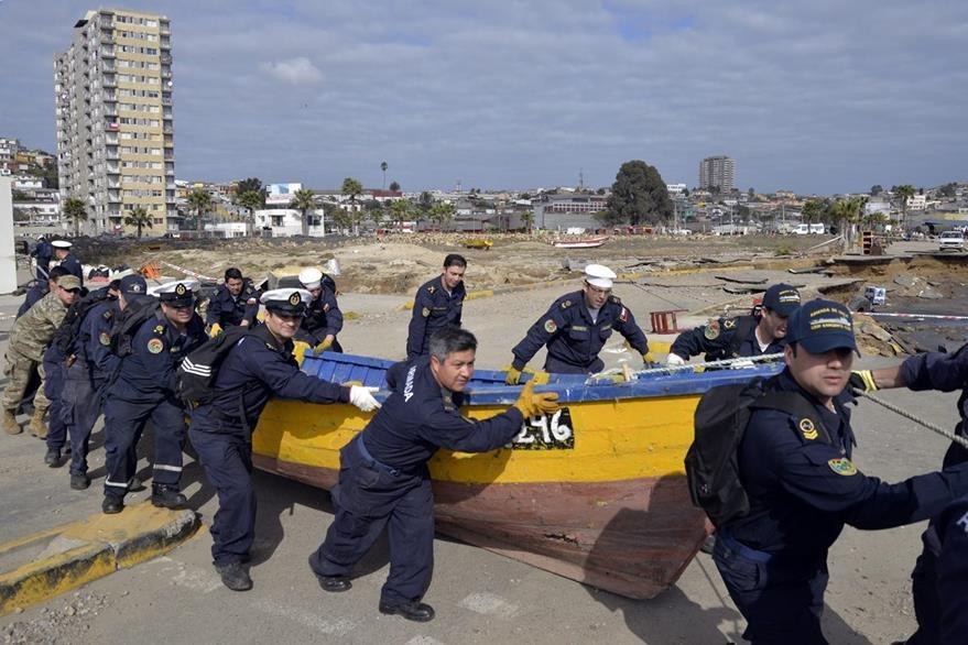 Marinos de la Armada de Chile en labores de limpieza tras el terremoto y tsunami en ese país. (Foto Prensa Libre: EFE).