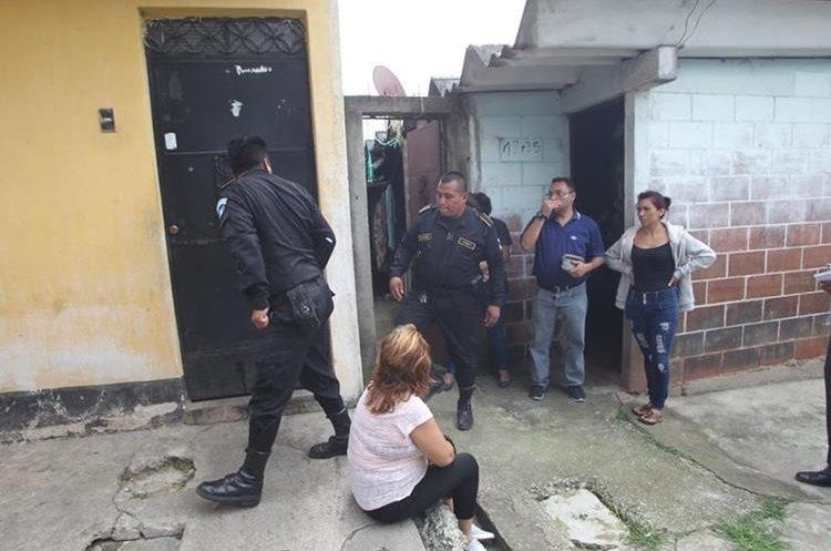Afuera de la residencia donde murió la mujer, una familiar observa mientras agentes de la PNC resguardan la escena. (Foto Prensa Libre: Érick Ávila)
