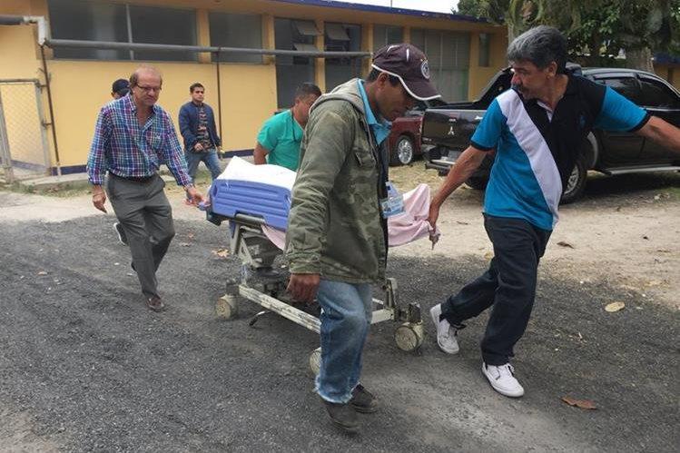 Empleados del Hospital Nacional de Jalapa, trasladan el cuerpo de Erick Tomás Portillo Lemus, de 54 años, quien murió baleado cuando se encontraba en una gasolinera. (Foto Prensa Libre: Hugo Oliva)