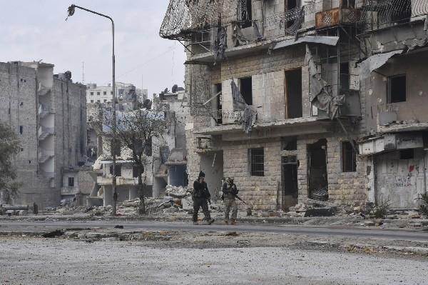 Soldados del ejército sirio patrullan las calles de Ansari, al este de Alepo. (AP).