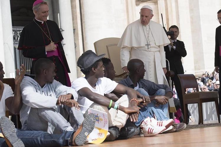 El papa Francisco observa a los refugiados que invitó a subir al escenario durante su audiencia general en el Vaticano. (Foto Prensa Libre: EFE).