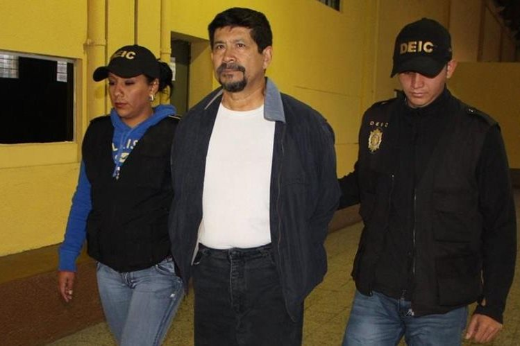 Uno de los capturados, sindicado de peculado y uso de documentos falsificados, es trasladado por la PNC. (Foto Prensa Libre: PNC)