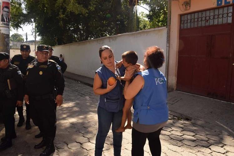 Agentes de la Policía Nacional Civil y delegadas de la PGN rescatan a uno de los menores. (Foto Prensa Libre: Víctor Gómez)