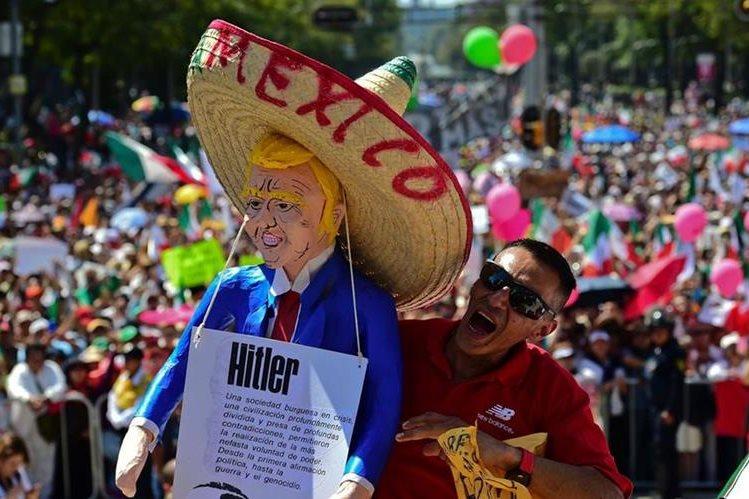 Un hombre sostiene una piñata que simula a Donald Trump y lo compara con el dictador Adolfo Hitler. AFP