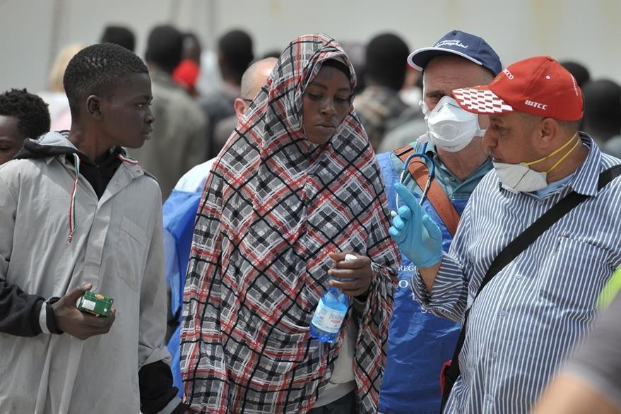 Migrantes africanos rescatados en el mar llegan a isla italiana. (AFP)