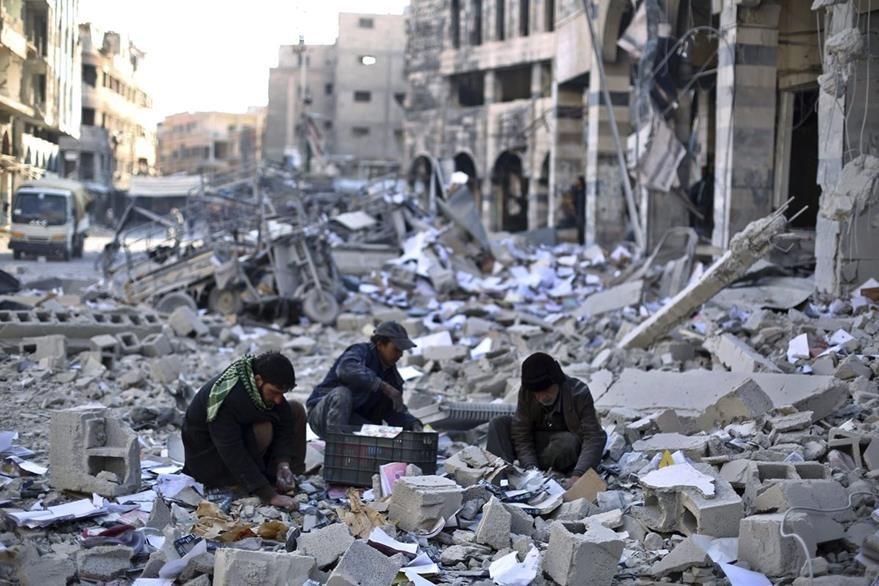 Varios hombres recogen objetos entre los escombros de un edificio en una calle de Douma, afueras de Damasco, Siria. Más de 260 mil han muerto en 4 años de conflicto.
