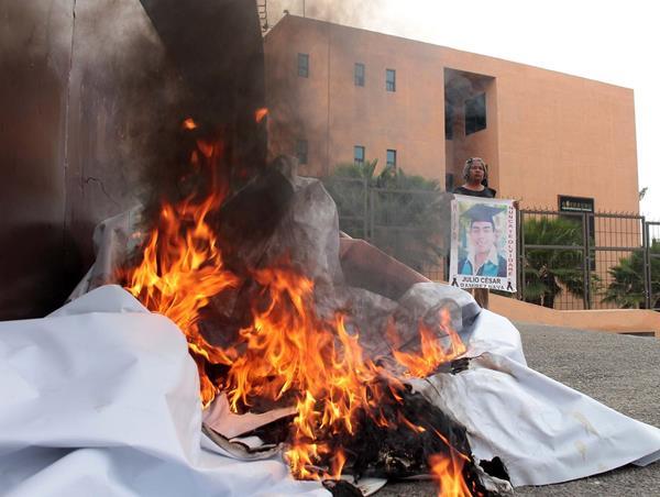 Una manifestante muestra la foto de uno de los desaparecidos en Guerrero. (Foto Prensa Libre: EFE)