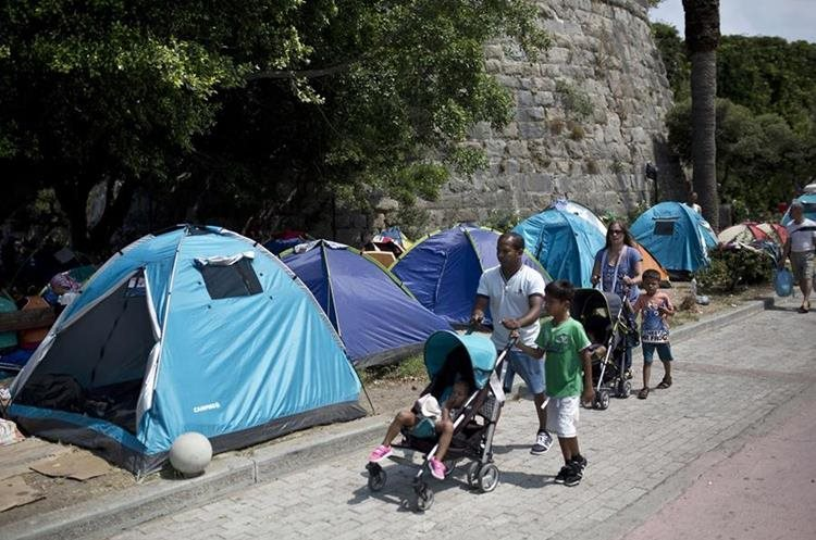 """People walk past tents of migrants set up in the street on the Greek island of Kos, on August 10 , 2015. The United Nations warned on August 7 that migrants landing in Greece were facing """"shameful"""" conditions, with the crisis-hit country claiming it was unable to cope with the massive influx on its Aegean islands. Some 124,000 people, almost all of them fleeing war and persecution in Syria, Afghanistan and Iraq, have come ashore since the beginning of the year -- a 750-percent increase from the same period last year. AFP PHOTO / ANGELOS TZORTZINIS"""