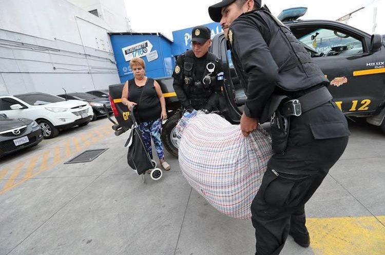 Una señora entrega un donativo de ropa. Agentes de policía le ayudan (Foto Prensa Libre: J. Ochoa).