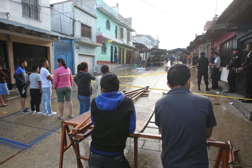 Vendedores del mercado Jocotales y vecinos del área, observan las diligencias de la PNC y MP, luego del asesinato del comerciante. (Foto Prensa Libre: Érick Ávila)