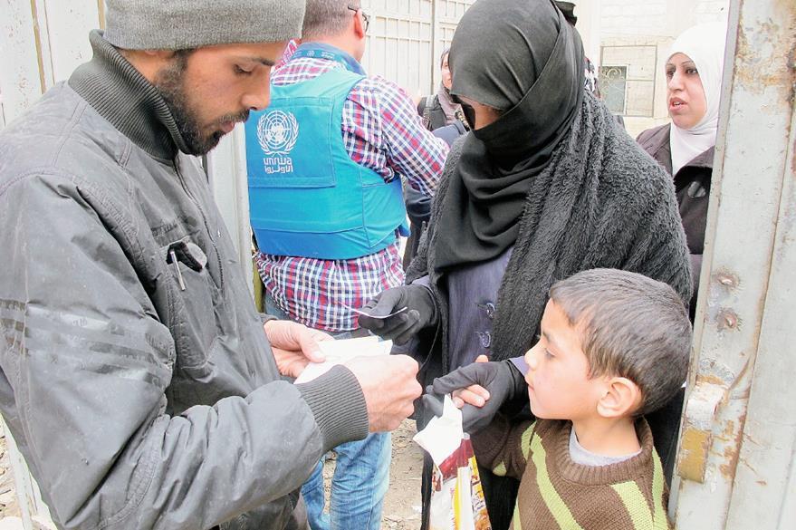 Refugiados sirios de Yarmuk reciben ayuda de la Agencia de Naciones Unidas de Obras y Socorro. (Foto Prensa Libre: AP).