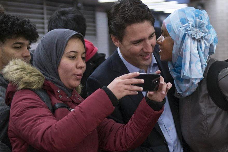 Una simpatizante besa a Justin Trudeau mientras otra musulmana se fotografía junto a él. (Foto Prensa Libre: AP).