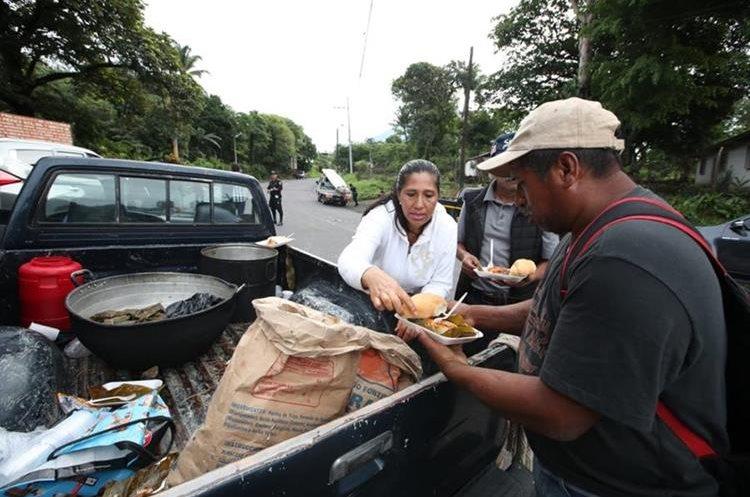 Voluntarios llevan desayuno a los presentes en el área de impacto de la erupción. (Foto Prensa Libre: Paulo Raquec)