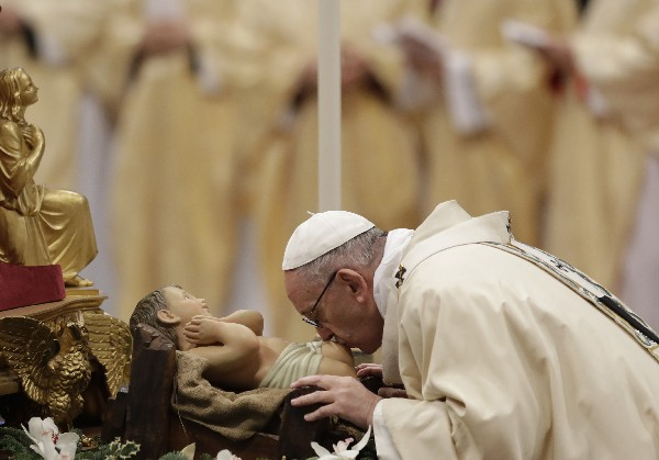 El Papa Francis besa una essultura del Niño jesús mientras celebra la misa en El Caticano. (AP).