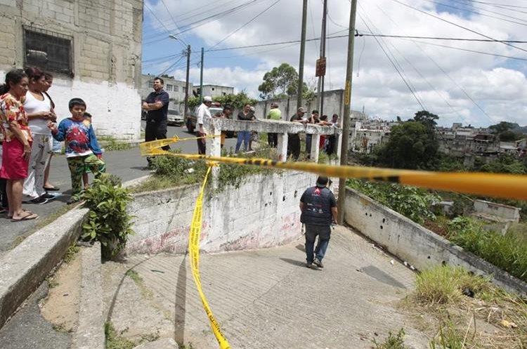 Un grupo de agentes de la PNC resguardan la entrada al asentamiento Positos, donde se registró la tragedia. (Foto Prensa Libre: Carlos Hernández)