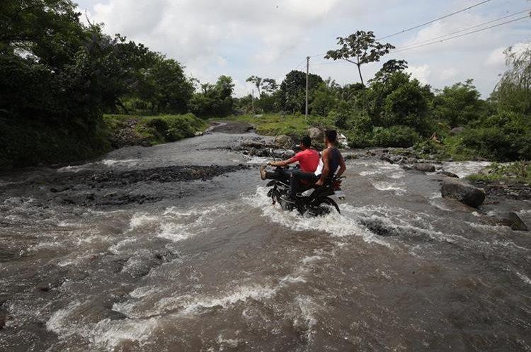 Pobladores de Yepocapa ponen en riesgo sus vidas al cruzar los ríos que interrumpen el camino.