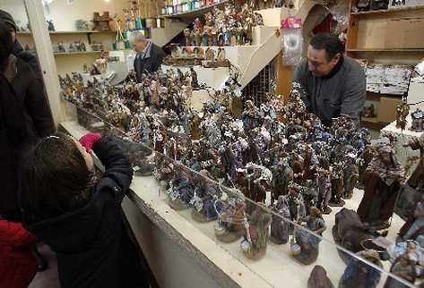 Una niña contempla las figuritas navideñas en uno de los puestos del mercadillo de Navidad de la Plaza Mayor en un día de niebla en la capital española (EFE)