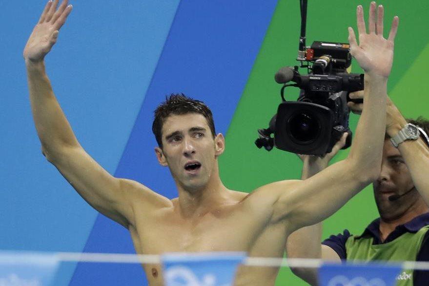 Michael Phelps alza los brazos para agradecer la ovación del público luego de conseguir la medalla dorada número 23. (Foto Prensa Libre: AP)