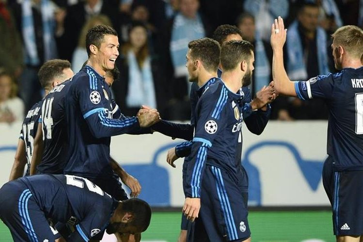 Los jugadores del Real Madrid felicitan a Cristiano Ronaldo luego de abrir el marcador al minuto 29. (Foto Prensa Libre:AFP)
