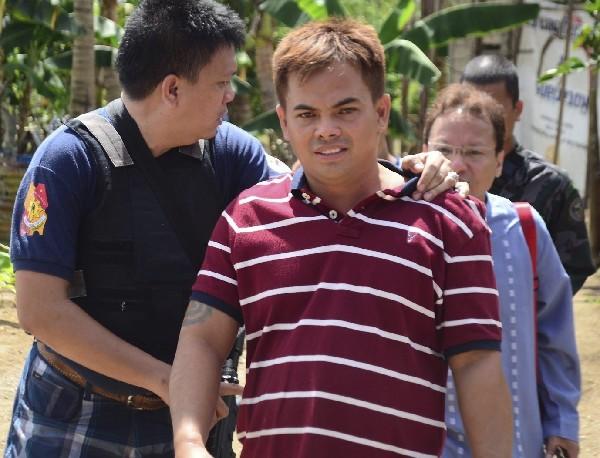 Erwin Espinosa (c) es escoltado por la Policía luego de ser arrestado. (EFE).