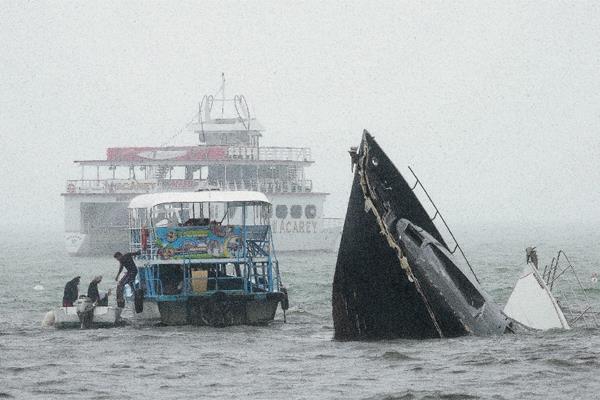 Un hombre se baja una lancha al lado de dos yates hundidos por el de huracán Carlos. (Foto Prensa Libre:AP).