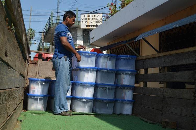 Bajan de camión cajas de plástico con papeletas en la JED, en la cabecera de Retalhuleu. (Foto Prensa Libre: Jorge Tizol)