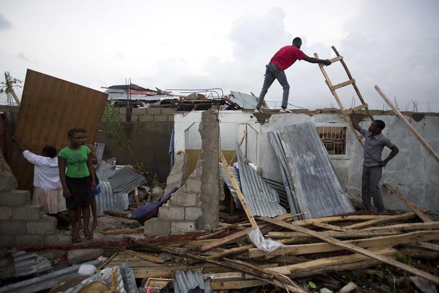 Haitianos remueven escombros en sus viviendas tras el paso del huracán. (Foto Prensa Libre: AP).