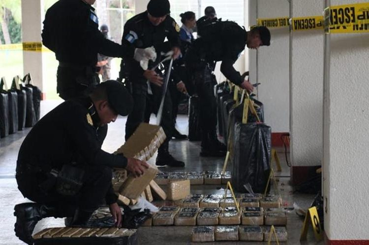 Autoridades antinarcóticas contabilizan la droga decomisada. (Foto Prensa Libre: PNC).
