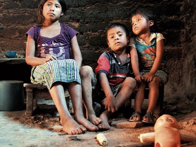 Los hijos de Santiago Martín Pérez esperan la hora de comer en su vivienda.