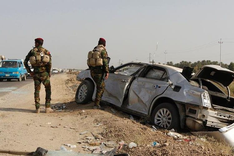 Soldados iraquíes inspeccionan el carrobomba utilizado por los yihadistas en el atentado. (Foto Prensa Libre: AFP).