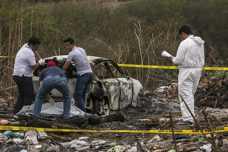 Forenses recaban evidencias en el vehículo que fue hallado en el lugar. (Foto Prensa Libre: EFE).