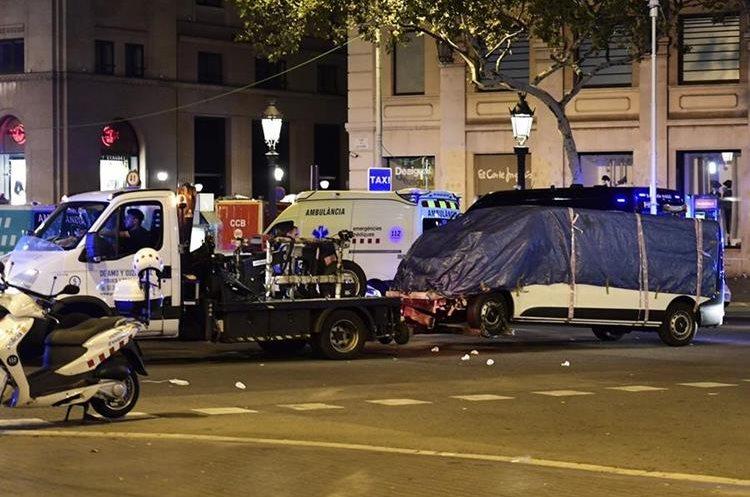 La furgoneta que atropelló a una multitud, matando al menos a 13 personas es remolcada de la Rambla de Barcelona. (AFP).