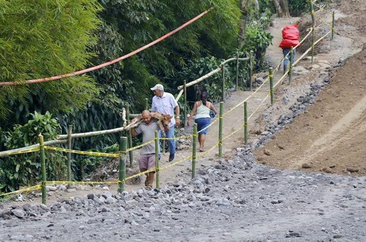 Pobladores utilizan un paso peatonal para pasar por el tramo afectado en la ruta de Retalhuleu a Quetzaltenango. (Foto Prensa Libre: Rolando Miranda)