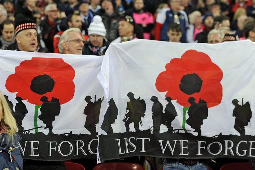 Aficionados de la selección escocesa de fútbol lucen pancartas en relación a la polémica desatada por el rechazo de la FIFA a permitir lucir la amapola, un símbolo en recuerdo de los caídos británicos en la Primera Guerra Mundial. (Foto Prensa Libre: EFE)