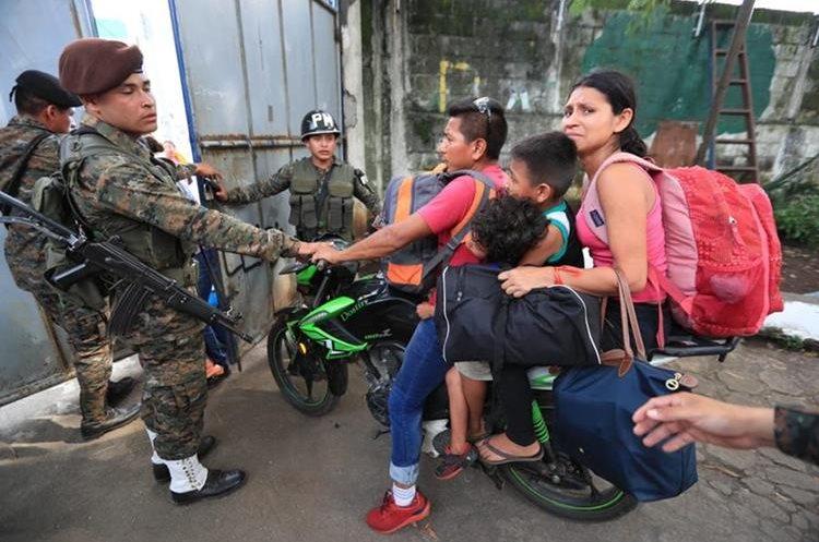 Un padre de familia intenta ingresar a un refugio con sus hijos y esposa.