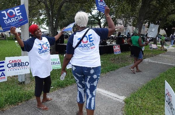 Voluntarios innvitan a las personas a votar en la Bahía de Cutler, Florida. (AFP).