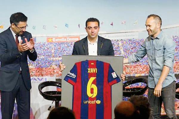 El presidente del Barcelona Josep María Bartomeu y Andrés Iniesta entregaron una camisola homenaje a Xavi. (Foto Prensa Libre: FC Barcelona)
