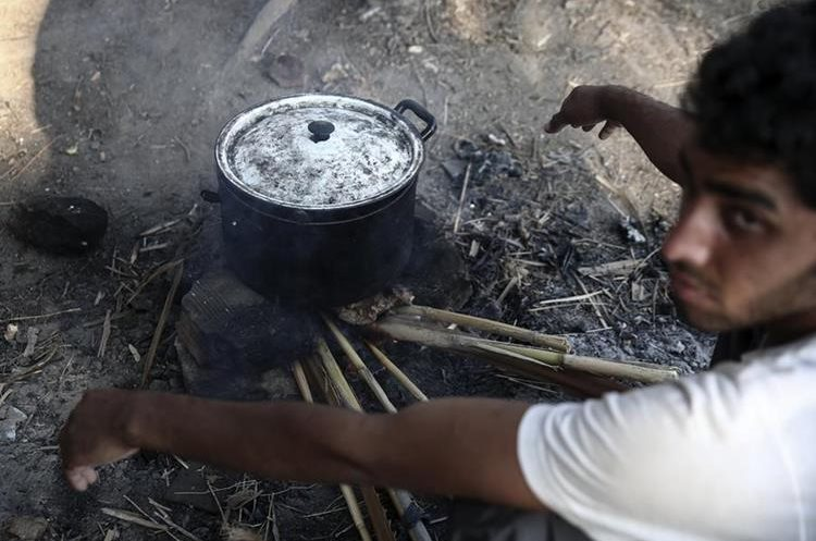 A migrant cooks outside an abandoned hotel where dozens of migrants have been living the last weeks at Kos town, on the southeastern island of Kos, Monday, Aug. 10, 2015. The European Union is granting 2.4 billion euros/$2.6 billion to EU nations to upgrade their migration programs with the biggest sums going to Greece and Italy where thousands of refugees have arrived this year. (AP Photo/Yorgos Karahalis)