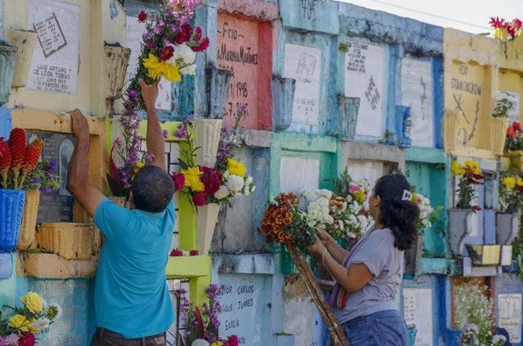 Mujer adorna tumba en el cementerio de Retalhuleu