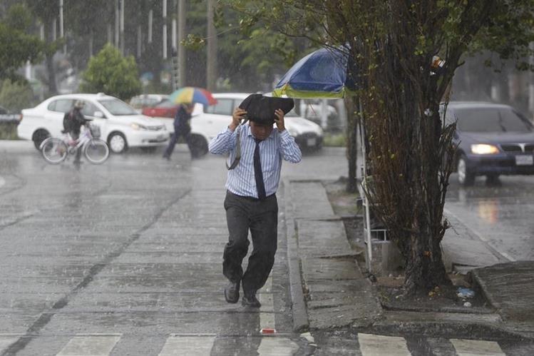 Un hombre se protege de la lluvia en una sector de la ciudad capital. Se espera que las precipitaciones aumenten en la tarde y noche. (Foto Prensa Libre: Hemeroteca PL)