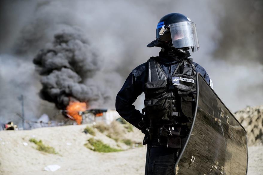 """Un policía antidisturbios vigila los alrededores durante el desmantelamiento del campamento conocido como """"La Jungla"""" de Calais (Francia) hoy, 26 de octubre de 2016. (Foto Prensa Libre: EFE)."""