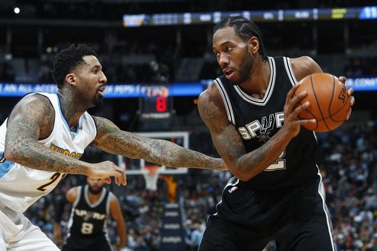 Wilson Chandler, de los Denver Nuggets, intenta detener a Kawhi Leonard de los Spurs, en el duelo que terminó ganando ayer San Antonio (Foto Prensa Libre: AP)